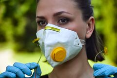 Girl in a protective mask sniffs a dandelion, COVID-19 coronavirus prevention, nature protection, quarantine time