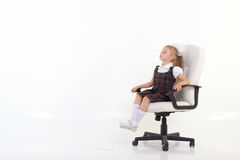 Girl proudly sits on a chair Stock Photo