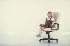Girl proudly sits on a chair Stock Images