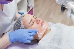 The girl is provided with an ultrasound skin cleaning service in the beauty salon stock images