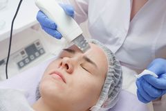 The girl is provided with an ultrasound skin cleaning service in the beauty salon royalty free stock photos