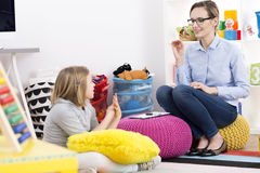 Girl and psychologist. Little blond girl visiting a school psychologist royalty free stock images