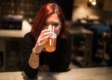 Girl in a pub drinking craft beer. Girl in a pub listening to his boyfriend drinking craft beer, having fun, smiling Royalty Free Stock Photo