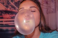 Bubble from chewing gum. The girl puffs up a huge white bubble of gum. Long blond hair, eyes closed. Home furnishings, evening, lilac tint Royalty Free Stock Image