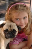 Girl with pug Stock Images