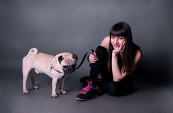 Girl with pug dog in studio. Beautiful sport brunette woman sitting on the floor and holding her pug dog on a leash in studio environment Stock Image