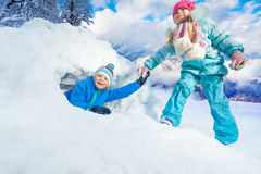 Girl pull boy out of snow cave in park Royalty Free Stock Photos