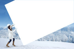 Girl pull empty billboard in winter day Royalty Free Stock Images