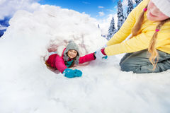 Girl pull on her friend from the snow cave Stock Photos