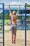 The girl pulled on the horizontal bar in the Park on the sports ground. Summer Stock Photos