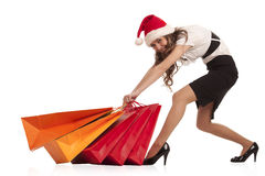 Girl pulling christmas shopping bags Royalty Free Stock Photo