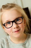 Girl pulling a funny face. Cute young girl in glasses pulling a funny face Royalty Free Stock Images
