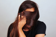 Girl Pulling Hair Across Face. Portrait of a young woman pulling her long brown hair across her face. Female is unrecognizable Stock Photos