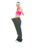 Girl pulling oversize jeans and showing thumbs up Stock Photos