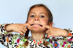 Girl pulling a silly face. Studio portrait of young girl pulling a silly contorted face royalty free stock images