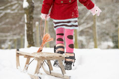 Girl Pulling Sledge Through Winter Landscape royalty free stock images