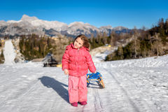 Girl is pulling snow sledge in ski resort  wearing winter clothe Stock Image