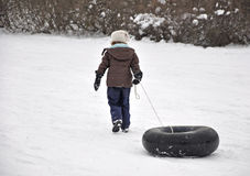 Girl pulling tube up sledding hill Royalty Free Stock Photography