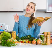 Girl in pullover learning new recipe from cookbook. Positive girl in pullover learning new recipe from cookbook Stock Image