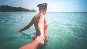 The girl pulls of a guy in the sea. The girl pulls the hand of a guy in the turquoise sea Stock Images