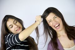 Girl pulls hard very long hair. To a friend Stock Photos