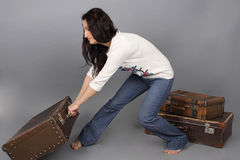 Girl pulls a huge suitcase. The girl in jeans and a white sweater Royalty Free Stock Photography