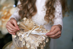Girl pulls the ribbon opening gift Stock Photos