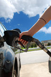 Girl pumping gas. A arm of a woman pumping gas Stock Image