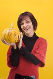 Girl and pumpkin. Young girl with a yellow pumpkin in her hands royalty free stock photos