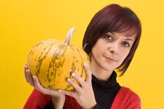 Girl and pumpkin. Young girl with a yellow pumpkin in her hands stock photos