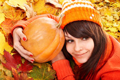 Girl with  pumpkin on autumn leaves. Stock Photo