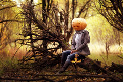 Girl with pumpkin head Royalty Free Stock Image