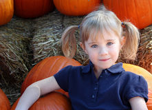 Girl in Pumpkin Patch. A little girl with pigtales smiles while sitting in a pumpkin patch Stock Image