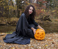 Girl with pumpkin by the river Royalty Free Stock Photography