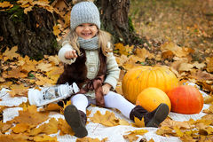 Girl with pumpkins on autumn background. Girl sitting on a blanket with pumpkins and a lantern on a background of yellow autumn leaves Royalty Free Stock Photos