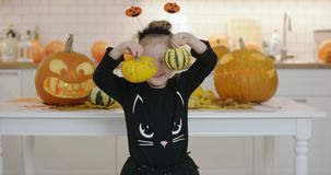Girl with pumpkins. Smiling little girl in cute Halloween costume standing in front white table with jack-o-lanterns and holding two small pumpkins stock video footage