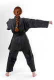 Girl punching in the black kimono, rear view Stock Photography