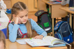 A girl pupil in classroom at school looking at a textbook. A girl pupil in the classroom at school looking at a textbook Royalty Free Stock Photo