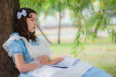 Girl pupil fell sleep under a tree with a book. Girl pupil in the image of a character from a fairy tale fell sleep under a tree with a book Royalty Free Stock Photo
