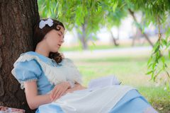 Girl pupil fell sleep under a tree with a book. Girl pupil in the image of a character from a fairy tale fell sleep under a tree with a book Stock Images