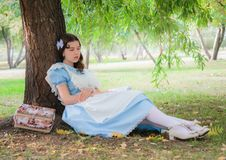 Girl pupil fell sleep under a tree with a book. Girl pupil in the image of a character from a fairy tale fell sleep under a tree with a book Stock Photos