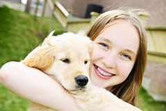 Girl with puppy. Portrait of smiling teenage girl holding golden retriever puppy Royalty Free Stock Image
