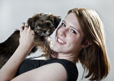 Girl with puppy. A pretty young woman holding a cute puppy by her face stock images