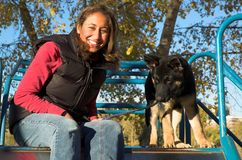 Girl and puppy. Young woman and her German Shepherd puppy ready to ride on a slide at the playground stock image