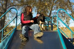 Girl and puppy. Young woman and her German Shepherd puppy ready to ride on a slide at the playground Royalty Free Stock Images