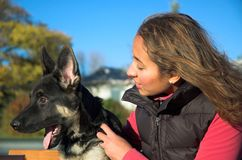Girl and puppy. Young woman and her German Shepherd puppy together on park bench royalty free stock image