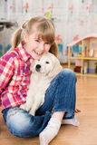 Girl and puppy friends Stock Image