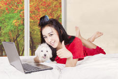 Girl with puppy showing thumb on camera. Image of pretty girl and puppy lying on the bed while smiling and showing thumb at camera with using a laptop in autumn Stock Photos