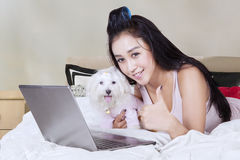 Girl with puppy showing thumbs up. Lovely girl showing thumb up and lying on the bed while embracing a maltese dog with laptop at home Stock Image