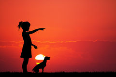 Girl and puppy at sunset Stock Photography